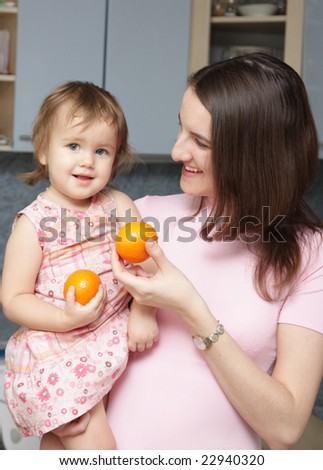 Mum treats a small daughter with oranges