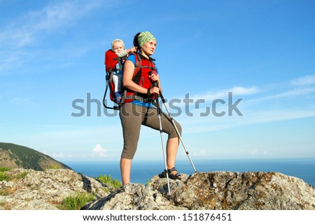Mum walks with the child in the child carrying it. - stock photo