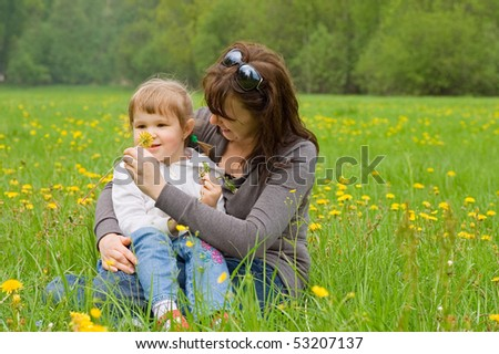 Mum with a daughter collect dandelions - stock photo