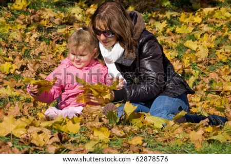 Mum with a daughter in autumn park - stock photo