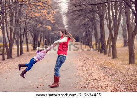 Mum with a daughter walk in autumn park. active rest. Autumn walk, November - stock photo