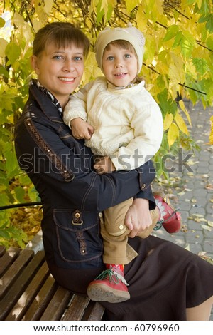 Mum with the child on a bench, autumn - stock photo