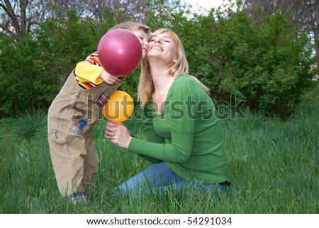 Mum with the son are played with balls in the spring on the nature - stock photo
