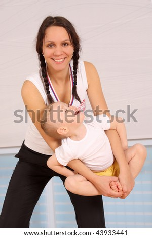 Mum with the son play a sports hall - stock photo