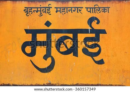 Mumbai city name on old yellow board in India - stock photo