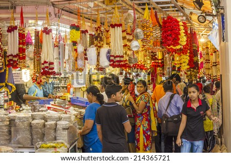 Mumbai, India - August 22, 2014 - People buying artificial flowers and garlands and gold ornament at shop at local market during Ganesha Festival - stock photo