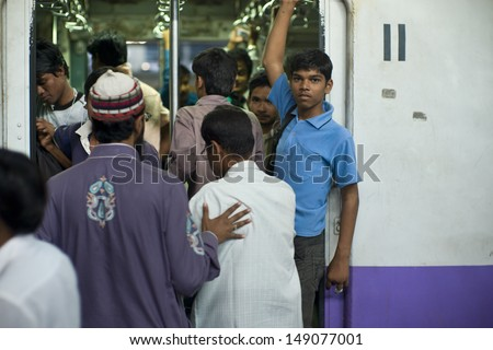 MUMBAI, INDIA - AUGUST 21: Unidentified locals and tourists commute by train on August 21, 2012 in Mumbai, India. Mumbai Suburban Railway carries more than 7 million commuters on a daily basis.