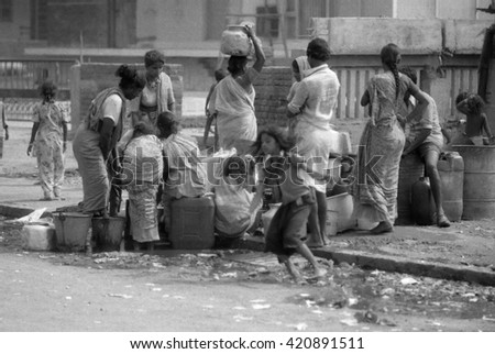 MUMBAI, INDIA - FEBRUARY 15, 1984: ladies collecting water from a fountain near the biggest open air city market. The place is everyday populated by thousands of people. - stock photo