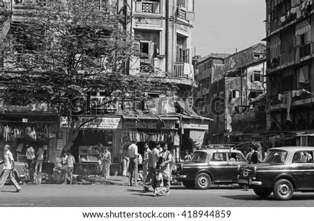 MUMBAI, INDIA - FEBRUARY 15, 1984: traffic and crowd of people in the city main street. The place is every day extremely crowded.