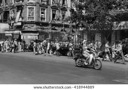 MUMBAI, INDIA - FEBRUARY 15, 1984: traffic and crowd of people in the city main street. The place is every day extremely crowded. - stock photo