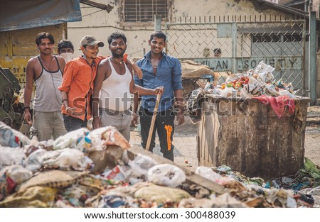 MUMBAI, INDIA - 16 JANUARY 2015: Five adult garbage men pile up garbage on slum street before throwing into garbage truck. Post-processed with grain, texture and colour effect. - stock photo