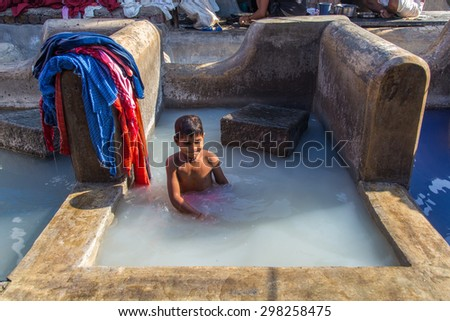 MUMBAI, INDIA - 10 JANUARY 2015: Indian child bathes in traditional laundromat pool in Dhobi Ghat. A well known open air laundromat in Mumbai. - stock photo