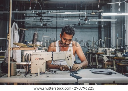 MUMBAI, INDIA - 12 JANUARY 2015: Indian worker sews in clothing factory in Dharavi slum. Post-processed with grain, texture and colour effect. - stock photo