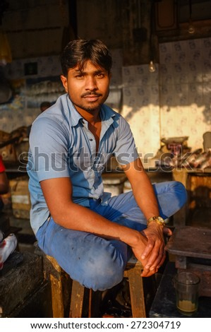 MUMBAI, INDIA - 08 JANUARY 2015: Worker at a fishmarket next to Dhobi ghat posing while waiting for customers. - stock photo