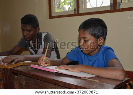 Mumbai, India - October 27, 2015 - Children from children's home learning and studying powered by chartiy project based in Europe, reading in books, writing and drawing