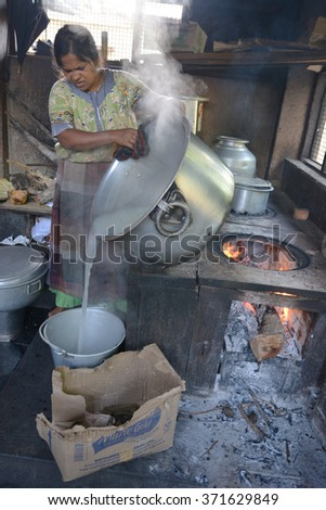 Mumbai, India - October 28, 2015 - Woman cooking rice in a traditional kitchen in India on open fire