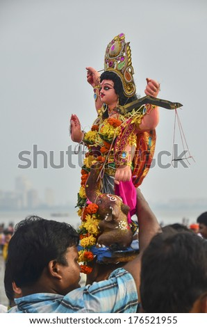 Mumbai, India - September17, 2013 - Devotees bringing Hindu God into the ocean with a blur foreground of burning incense and flowers as offerings during Ganesha Festival