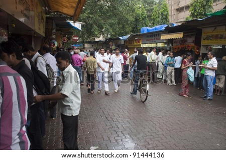 MUMBAI, INDIA - SEPTEMBER 6: Unidentified locals eat at street food stalls on September 6, 2011 in Mumbai, India. Mumbai is famous for its street food. Stalls offer  delightful variety of meals. - stock photo