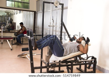 MUMBAI, MAHARASHTRA, INDIA, 3 MAY 2016 : Unidentified young men  working out on fitness equipment at gym. group of men with dumbbells in gym.