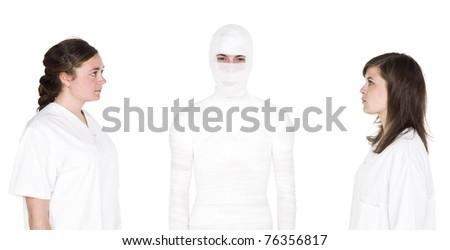 Mummified person with two female nurses - stock photo