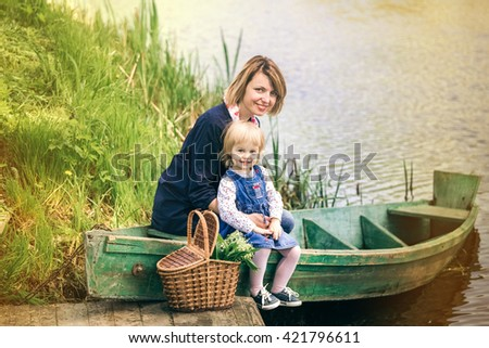 Mummy and adorable small child playing together in old wooden boat on river. Portrait of happy family over scenic nature background. Mother and little girl on picnic during vacations. - stock photo