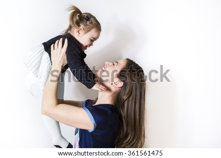 mummy and her kid on a white wall - stock photo