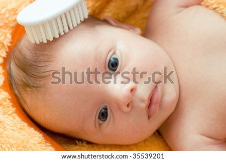 Mummy brushing her son with comb - stock photo