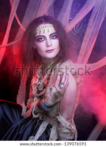 Mummy. Young woman in creative image posing with smoke