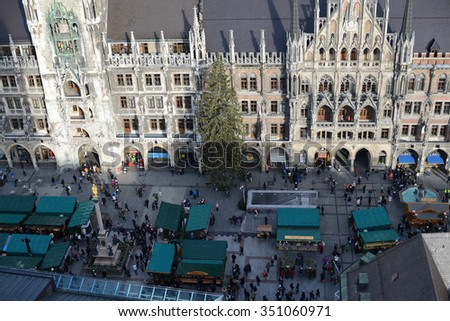 MUNICH, BAVARIA/ GERMANY December 14 2015: Christmas market on Munich Marienplatz in centre of city. Lot of people walking across the place. Munich town hall with huge christmas tree in the background - stock photo
