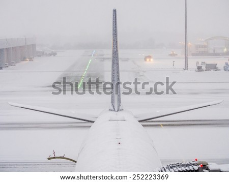 Munich - 30 dec 2014: Airbus 340 plane details, parked at the terminal under heavy snow, wait to be prepared by the operators for takeoff - stock photo