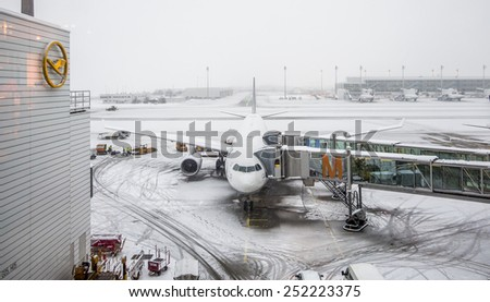 Munich - 30 dec 2014: Airbus 340 plane parked at the terminal under heavy snow, wait to be prepared by the operators for takeoff - stock photo