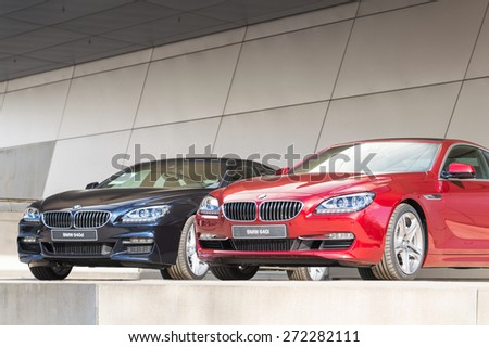 MUNICH, GERMANY - APRIL 12, 2015: New modern BMW 640 model lineup of first class exclusive business sedan cars. Front view of dark blue 640d and red 640i. - stock photo