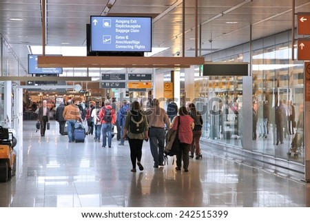 MUNICH, GERMANY - APRIL 1, 2014: Travelers walk to gates at Munich International Airport in Germany. It was the 7th busiest airport in Europe with 38,360,604 passengers in 2012. - stock photo