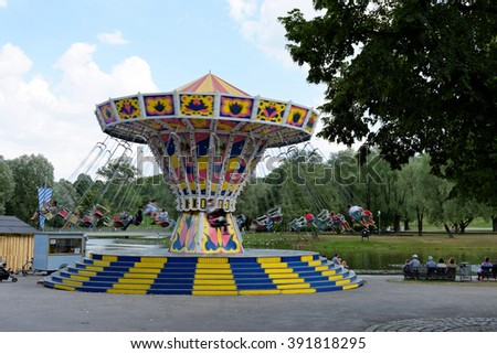 MUNICH, GERMANY - 4 AUGUST 2015: Chains carousel in a fun fair on the grounds of the Olimpiapark near Olympia Tower. - stock photo