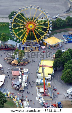 MUNICH, GERMANY - 4 AUGUST 2015: Ferris Wheel in a fun fair on the grounds of the Olimpiapark near Olympia Tower. - stock photo
