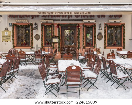 MUNICH,GERMANY- DEC 19: Image of a terrace covered by snow in front of the entrance in a traditional Bavarian Restaurant in Munich,Germany on 19 December 2014.  - stock photo