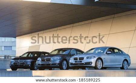 MUNICH, GERMANY - DECEMBER 27, 2013: New collection of powerful BMW 535 business and family classes. Three wet after rain cars - the entire model line: sedan, liftback, station wagon. - stock photo