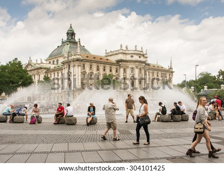 MUNICH, GERMANY - JULY 20: Tourists at Stachus fountain in Munich, Germany on July 20, 2015. Munich is the biggest city of Bavaria  with almost 100 million visitors a year.  - stock photo