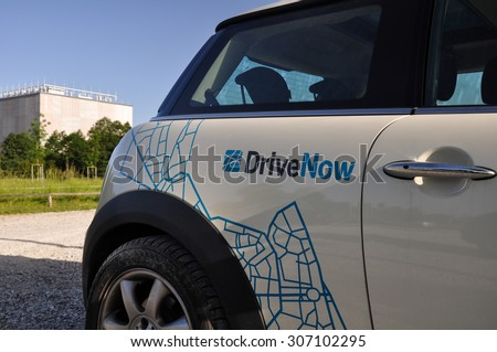 "Munich, Germany - June 08, 2014: ""DriveNow"" logo on a parked MINI Cooper in Munich. ""DriveNow"" is a car sharing company owned by BMW. Members can book available cars and pay per minute of use."