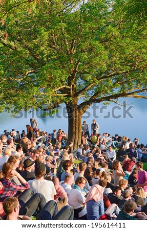 MUNICH, GERMANY - MAY 25, 2014:  After a long winter crowds of fans come out to a early summer music concert at the Olympic Park in Munich. - stock photo