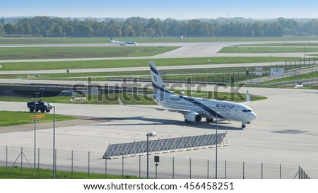 Munich, Germany - May 6, 2016: Israeli airline El Al plane landed in international airport and taxiing from runway to terminal accompanied by security armored vehicle. - stock photo
