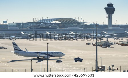 Munich, Germany - May 6, 2016: Israeli passenger plane El Al Airlines accompanied by anti terrorism police armored vehicle taxiing to international airport terminal. - stock photo