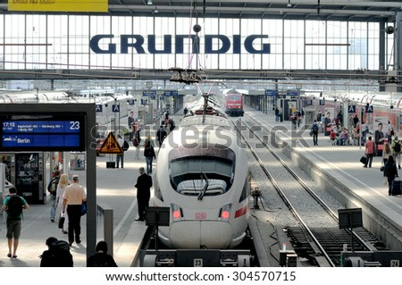 MUNICH, GERMANY - MAY 25, 2010: Main Munich central train station platform view, with a high speed ICE train and commuters on platform at Hauptbahnhof - stock photo