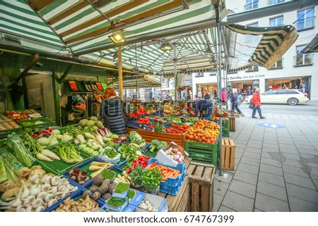 MUNICH, GERMANY - MAY 9, 2017 : People buying fruit and vegetable at the outdoor food market near Marienplatz in Munich, Germany.