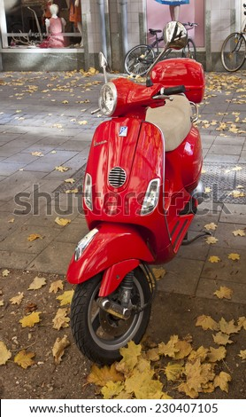 MUNICH, GERMANY - NOVEMBER 4,2014.Vintage red Vespa,old fashioned Italian motorbike, is parked on the street sideway in Munich center - stock photo