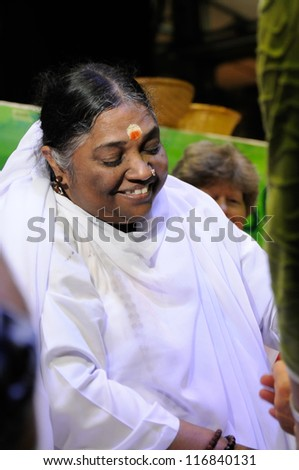 MUNICH, GERMANY - OCT 28: Amma, Mata Amritanandamayi, a famous hindi avatar, embracing people during her Embracing the world Tour in Zenith Hall, Munich, Germany on October 28, 2011.