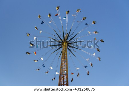 MUNICH, GERMANY - OCTOBER 02, 2015: Carousel in motion with people flying through the air on Theresienwiese - stock photo