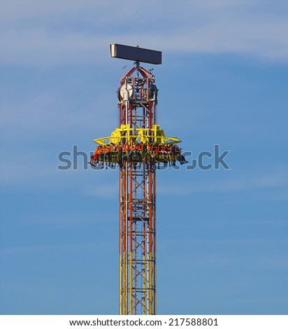 MUNICH, GERMANY - OCTOBER 3, 2010. People wait up in the blue sky for the vertical ride and  the zero gravity thrill to begin, at Oktoberfest amusement park on Marienwiese in Munich. - stock photo