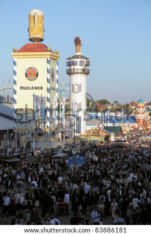 MUNICH, GERMANY – OCTOBER 03: View over the Oktoberfest with crowds of visitors. Towers of the Bavarian beer brands Paulaner and Löwenbräu for advertising in Munich on October 03, 2010. - stock photo
