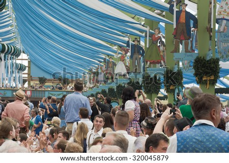 MUNICH, GERMANY - SEPT. 19, 2015:  Oktoberfest Crowds of Visitors at the Spatenbrau Tent celebrating the festivities.  The Festival runs from September 19th until October 4th 2015 in Munich, Germany. - stock photo